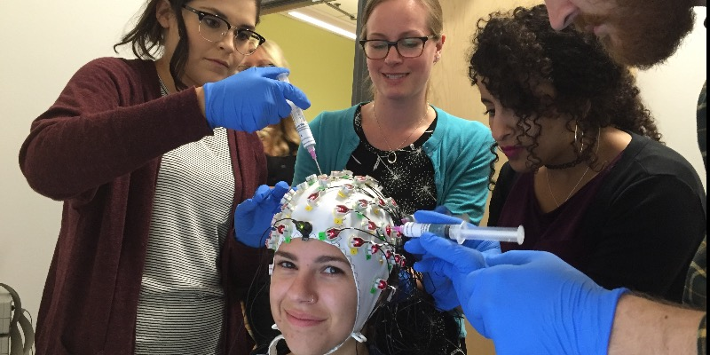 Dr. Lorna Quandt (center standing) performing an EEG demo experiment with Gallaudet University PhD in Educational Neuroscience students.